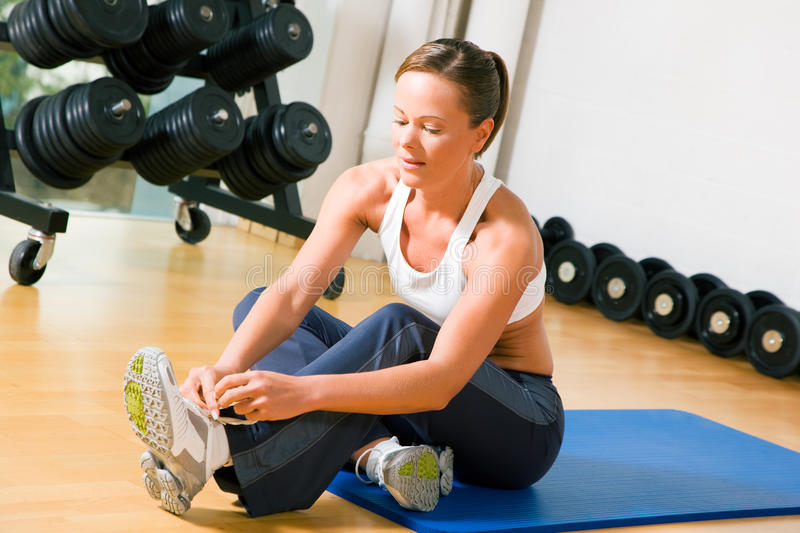 Tying shoelaces before training in gym. Woman tying her shoelaces before starting her workout in the gym stock photos