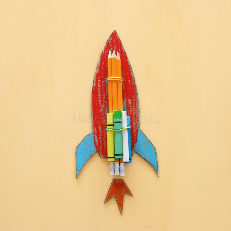 tylna koncepcji do szkoły karton rakiety cięcie od papierowego i malujący nad drewnianym żółtym tłem fotografia stock