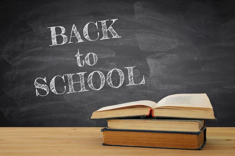 tylna koncepcji do szkoły sterta książki nad drewnianym biurkiem przed blackboard zdjęcia royalty free
