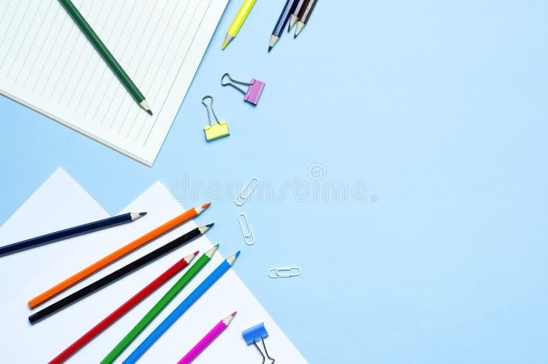 tylna koncepcji do szko?y Drewniani barwioni ołówki, czysty szkolny notatnik w linii, papierowe klamerki na błękitnym tło odgórne obraz royalty free