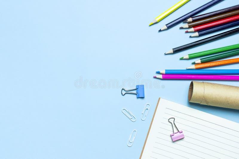 tylna koncepcji do szko?y Drewniani barwioni ołówki, czysty szkolny notatnik w linii, papierowe klamerki na błękitnym tło odgórne obrazy stock