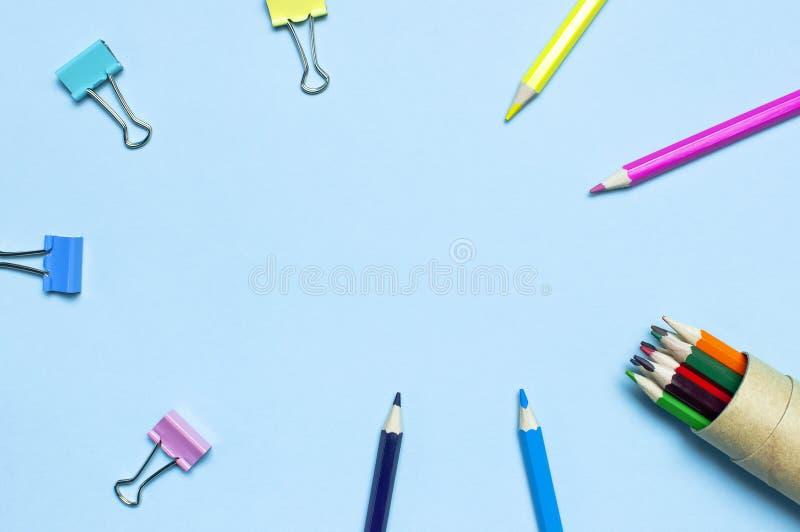 tylna koncepcji do szko?y Drewniani barwioni ołówki, papierowe klamerki na błękitnym tło odgórnego widoku mieszkaniu kłaść kopii  zdjęcie royalty free