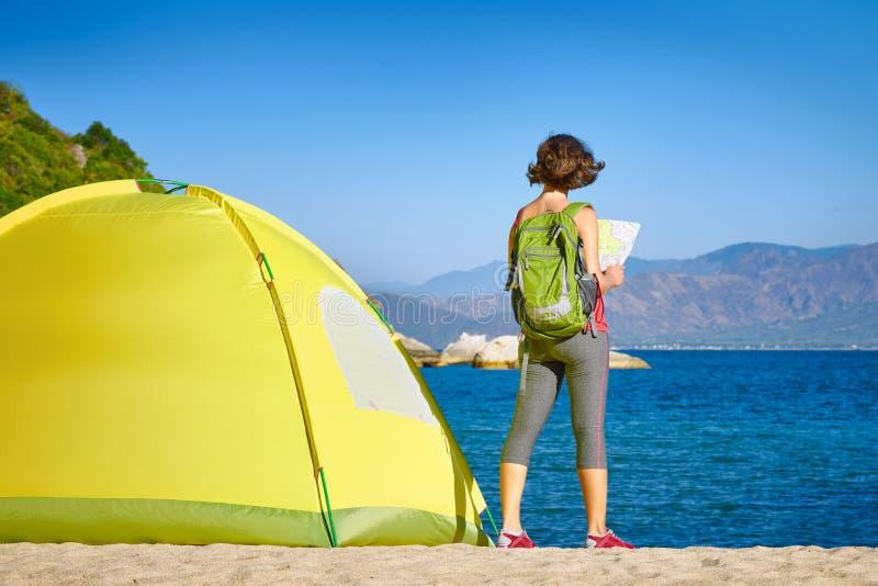 Tylna strona backpacker dziewczyny gmerania właściwa wskazówka na mapie zdjęcie stock
