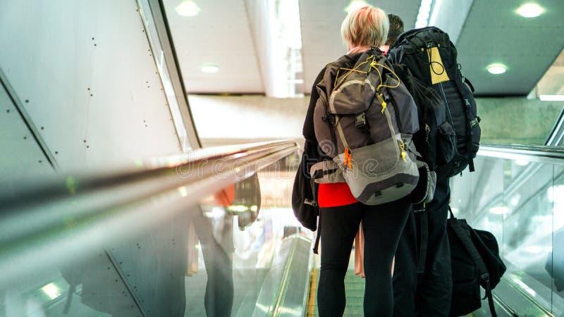 Tylna strona pary backpacker używa eskalator w lotnisku dla podróży i kopii przestrzeni obraz royalty free