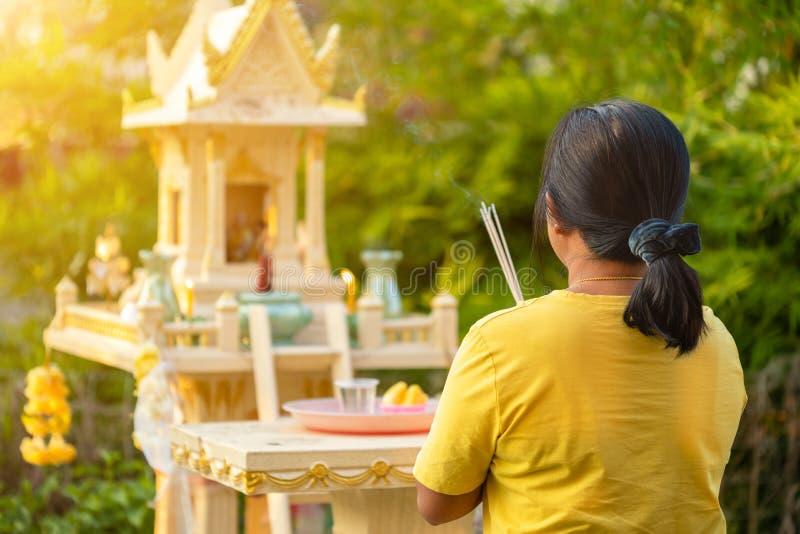 Tylna strona tajskiej kobiety stojącej przed domem joss i modlącej się kadzidłem zdjęcia stock