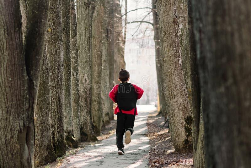 tylna szko?y Chłopiec w czerwonej bluzie sportowej z plecakiem na jego tylnych bieg zestrzela aleję Szczęśliwy dzieciństwo w szko obraz stock