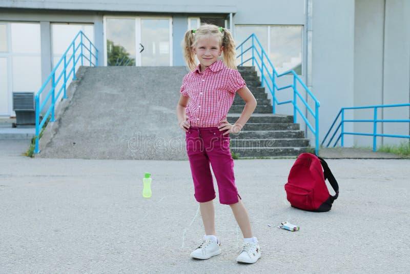 tylna szko?y Piękna blond uczennica z czerwoną plecak sztuką na zewnątrz szkoły podstawowej, edukacji pojęcie zdjęcie royalty free