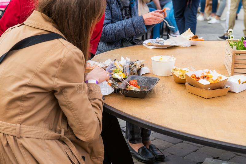 Tylna widok grupa ludzi odwiedza jedzenie rynek i je, festiwal, wydarzenie bierze oddalonego posiłek na karmowym sądzie w ulicie  fotografia stock