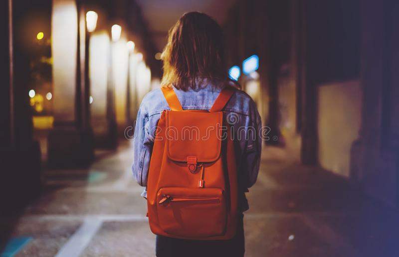 Tylna widok kobieta z plecakiem na tła bokeh świetle w nocy atmosferycznym mieście, blogger modnisia heblowania wakacyjna podróż, zdjęcia royalty free