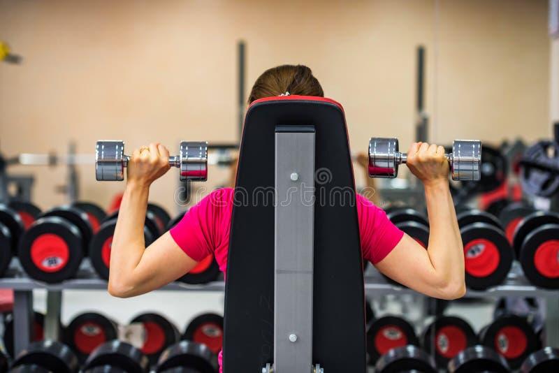 Tylna widok młoda kobieta trenuje deltoid w gym obrazy royalty free