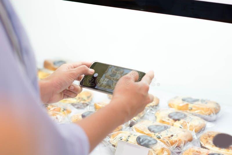 Tylni widok ?e?ski bierze obrazek chleb i piekarnia przy supermarketem, kobieta bierze fotografi? tort zdjęcie royalty free