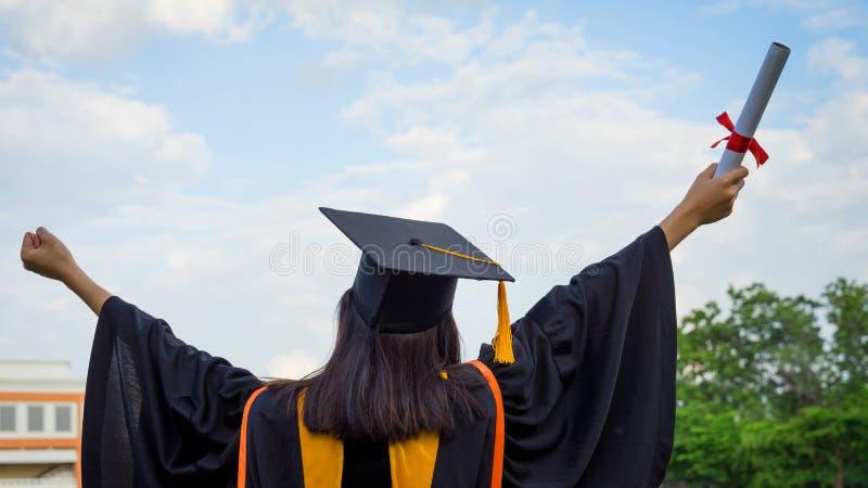 Tylni widok żeński uniwersyteta absolwent stoi stopnia świadectwo świętować w skalowanie ceremonii z jasnym i trzyma zdjęcia royalty free