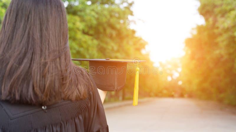 Tylni widok żeński uniwersyteta absolwent stoi stopnia świadectwo świętować w skalowanie ceremonii z jasnym i trzyma zdjęcie royalty free