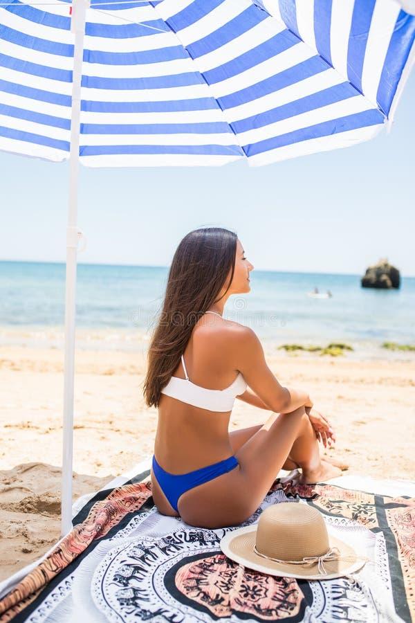 Tylni widok Atrakcyjna kobieta z garbnikującą skórą pozuje przy plażą w słonecznym dniu Portret od plecy elegancka dziewczyna w b obraz royalty free