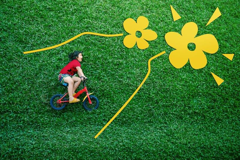 Tylni widok azjaty Szczęśliwi dzieciaki Dziewczyna na bicyklu Kłaść puszek przy Zielonym gazonem w wiośnie lub letnim dniu zdjęcie stock