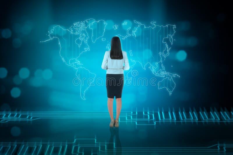 Tylni widok azjatykcia biznesowa kobieta patrzeje biznesową sieć zdjęcie stock