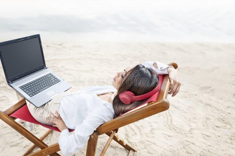 Tylni widok azjatykcia biznesowa kobieta siedzi relaksuje gdy pracujący z laptopem na plaży podczas gdy używać hełmofon w plażowy zdjęcie stock