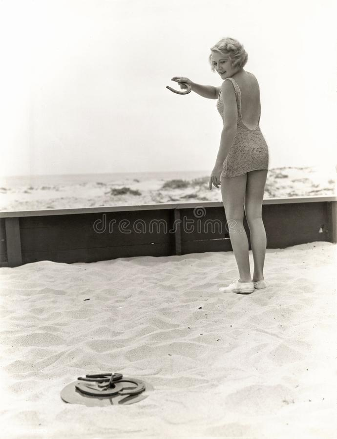 Tylni widok bawić się podkowy przy plażą kobieta fotografia royalty free
