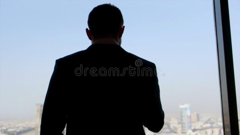Tylni widok biznesmen w kostium pozycji z jego smartphone w r?ce, patrzeje z okno zapas firma fotografia stock