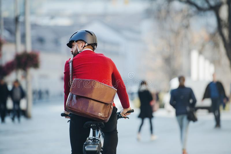 Tylni widok biznesmena dojeżdżający z elektryczny rowerowy podróżować pracować w mieście obraz stock