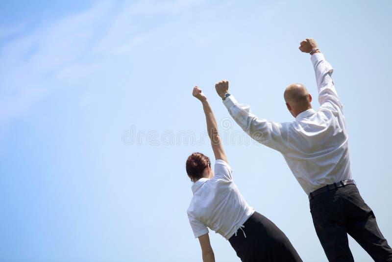 Tylni widok biznesowa para z rękami szeroko rozpościerać pozycję w parku zdjęcia stock