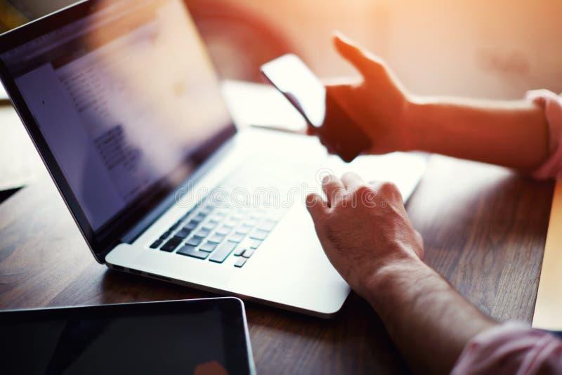 Tylni widok biznesowy mężczyzna wręcza ruchliwie używa telefon komórkowego przy biurowym biurkiem zdjęcie stock