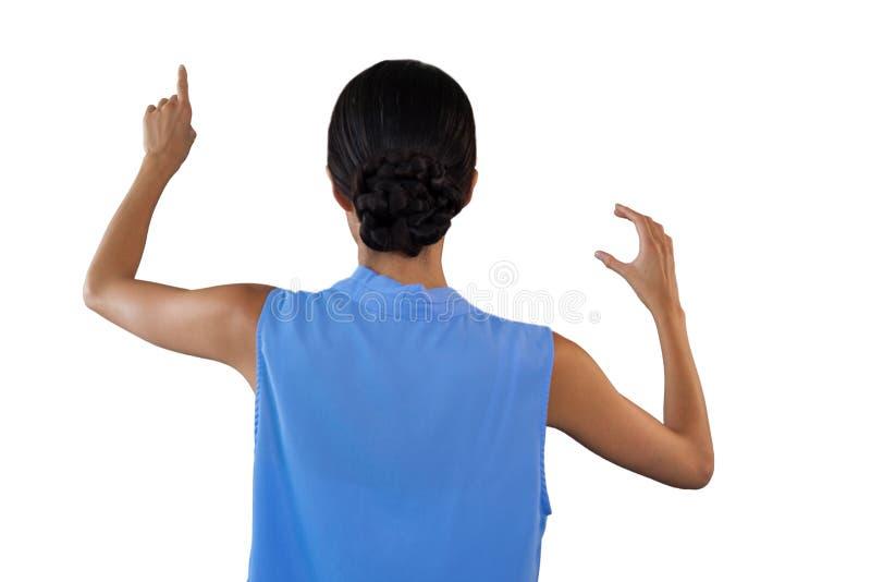 Tylni widok bizneswomanu wzruszający interfejs podczas gdy trzymający coś obraz royalty free