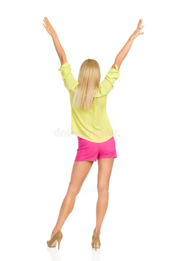 Tylni widok Blond kobiety pozyci nogi Z rękami Podnosić Oddzielnie zdjęcie royalty free