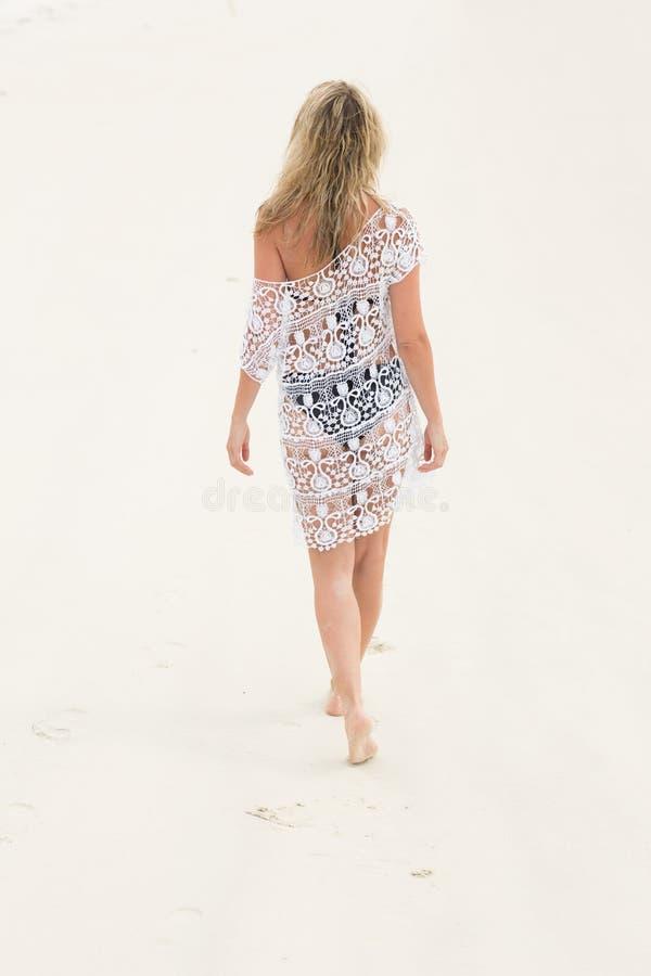 Tylni widok blondynki kobieta w odprowadzeniu na plaży fotografia stock