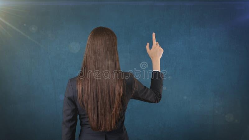 Tylni widok długi ciemnego włosy piękno wskazuje lub przedstawia na jej prawej stronie obrazy stock