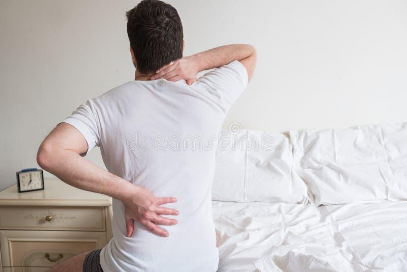 Tylni widok jeden mężczyzna obsiadanie na łóżku ma ból pleców zdjęcie royalty free