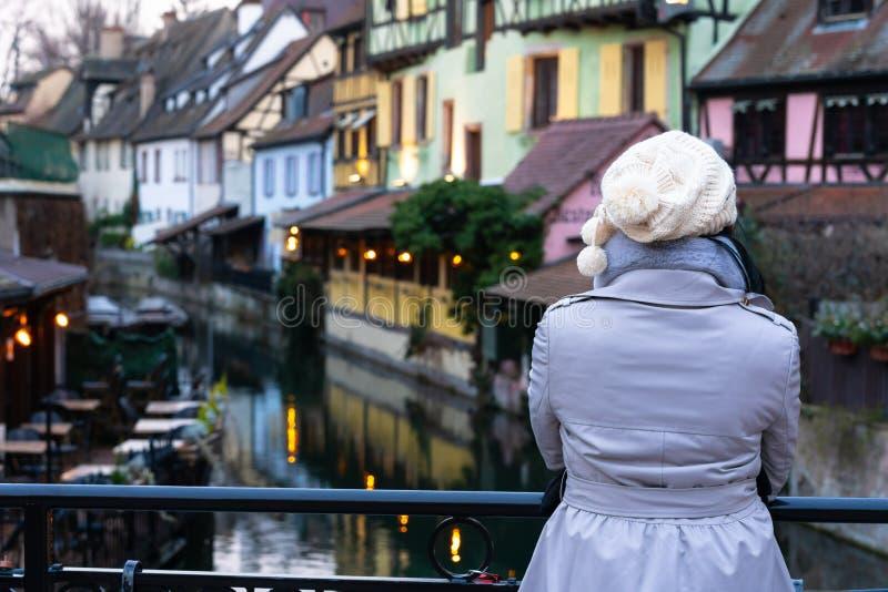 Tylni widok jest ubranym topcoat na stronie kanałowy patrzeć Kolorowi tradycyjni starzy francuzów domy na Lauch przy parzysty, ró zdjęcia stock