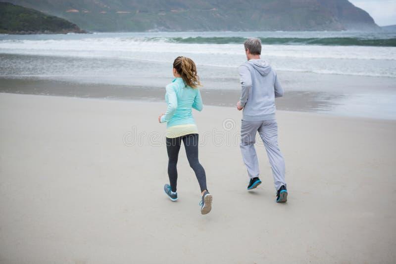 Tylni widok jogging na plaży para obrazy royalty free