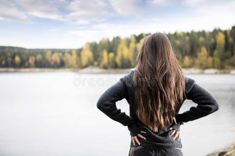 Tylni widok kobieta Stoi jeziorem Z rękami Na biodrach obraz royalty free
