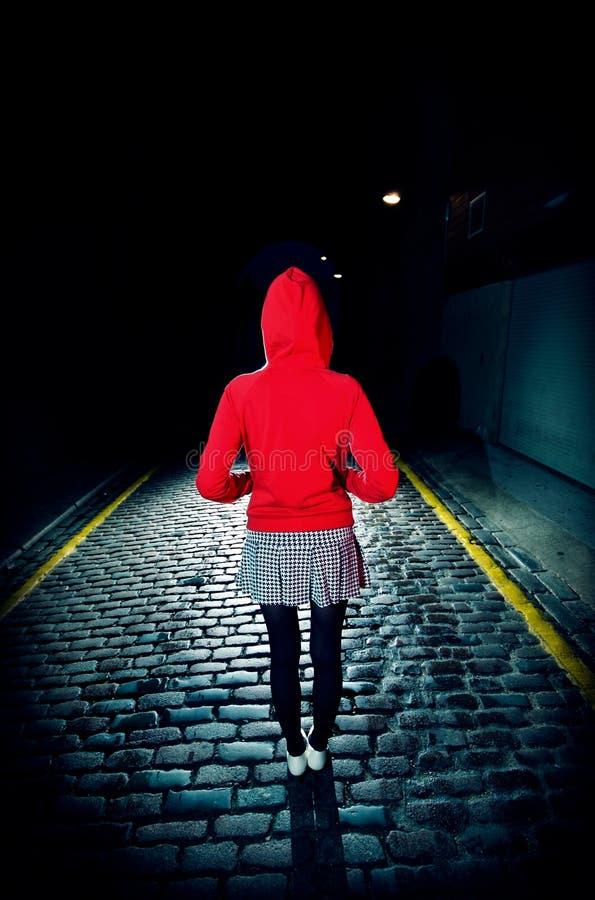 Tylni widok kobieta W Czerwonym kapiszonie Na ulicie Przy nocą obrazy stock