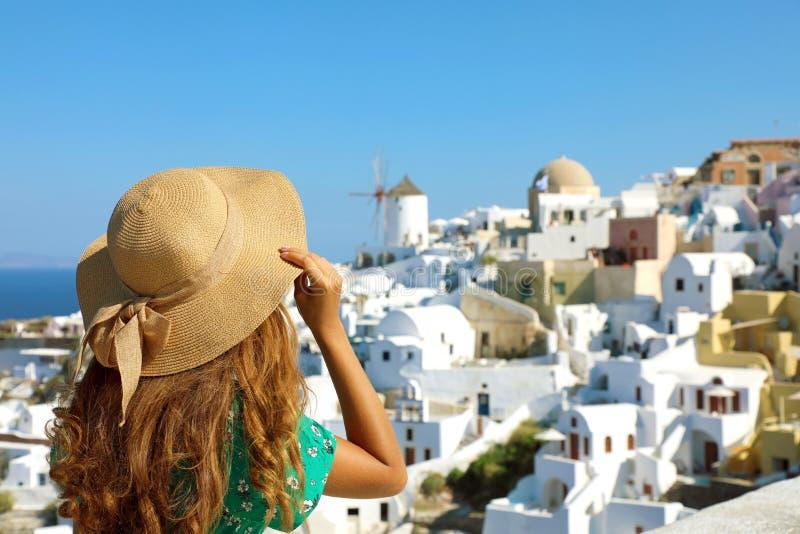 Tylni widok kobieta z kapeluszową patrzeje Oia wioską w Santorini wyspie w morzu śródziemnomorskim, Grecja Podróżować w Europa obrazy royalty free