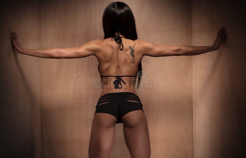 Tylni widok kobiety macania Sportowe ściany fotografia royalty free