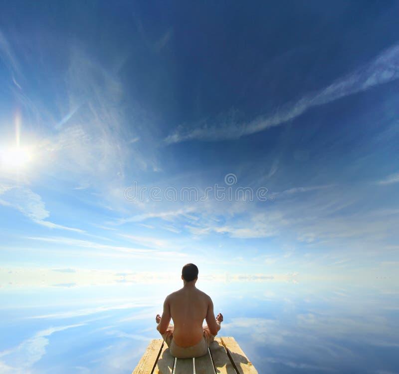 Tylni widok mężczyzna Medytuje w Lotosowej joga pozyci przy brzeg rzeki zdjęcie stock