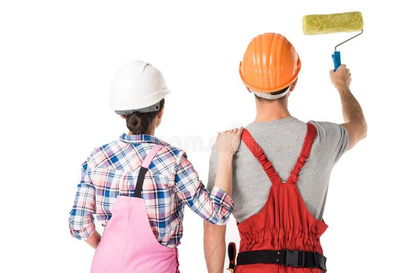 Tylni widok męscy i żeńscy budowniczowie pracuje z farba rolownikiem obrazy stock