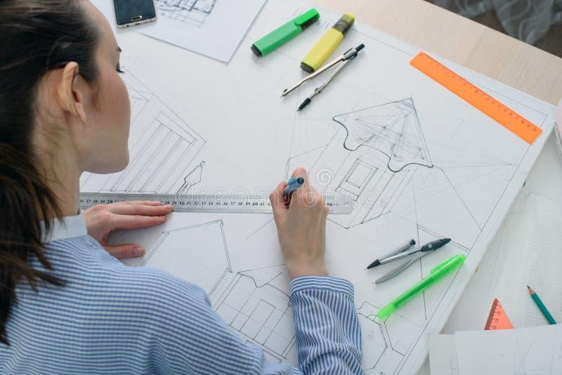 Tylni widok młoda kobieta przygotowywa architektoniczną pracę przy stołem z rysownicą, władcą i ołówkiem białymi, obraz royalty free