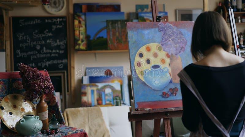 Tylni widok Młoda malarz dziewczyna maluje wciąż życie obrazek na kanwie w klasie w fartuchu obrazy stock