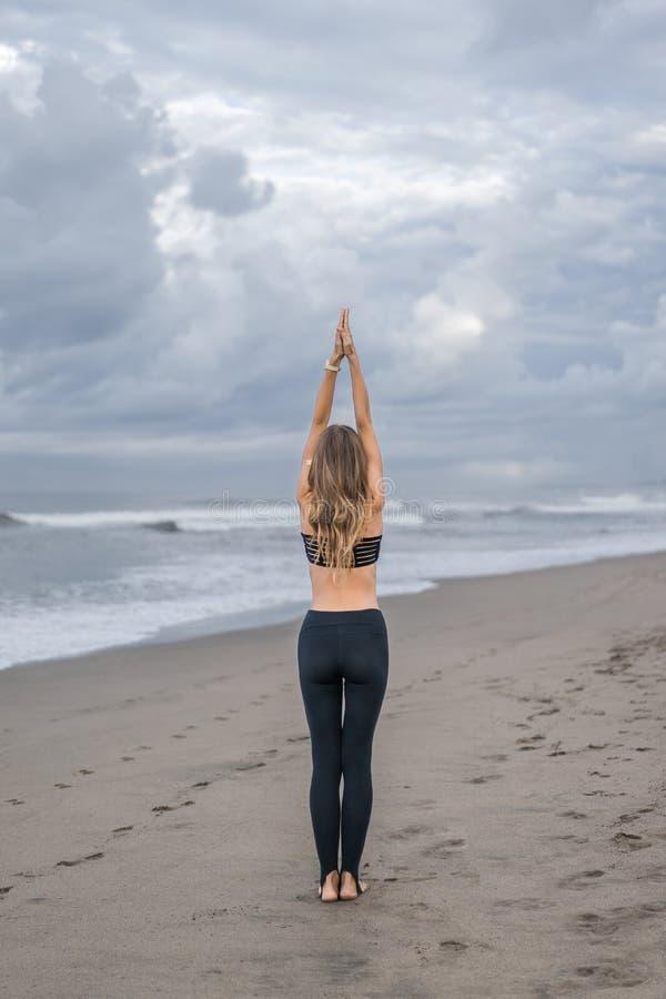 tylni widok młodej kobiety ćwiczy joga w Halnej pozie na seashore (Tadasana) fotografia royalty free