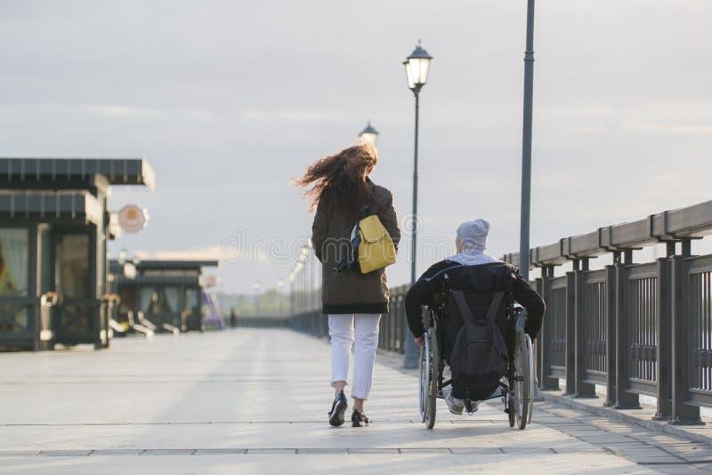 Tylni widok młodej kobiety odprowadzenie z niepełnosprawnym mężczyzna w wózku inwalidzkim na quay fotografia stock