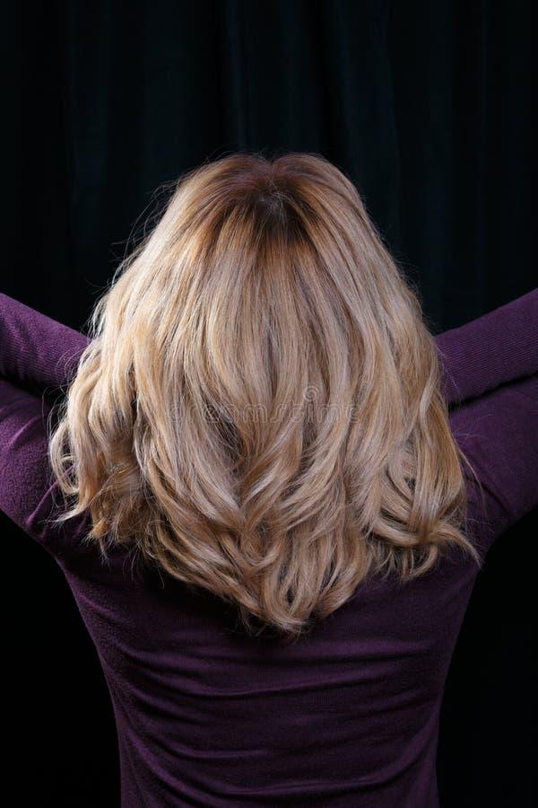 Tylni widok na kobiecie z elegancką kędzierzawą fryzurą Rozwijać twój włosy fotografia stock