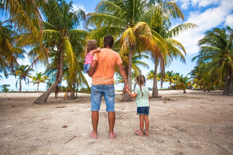 Tylni widok ojciec z dwa dzieciakami chodzi przy plażą obraz royalty free