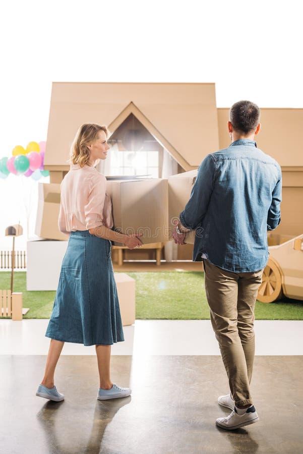 tylni widok pary chodzenie w nowego kartonu dom fotografia stock
