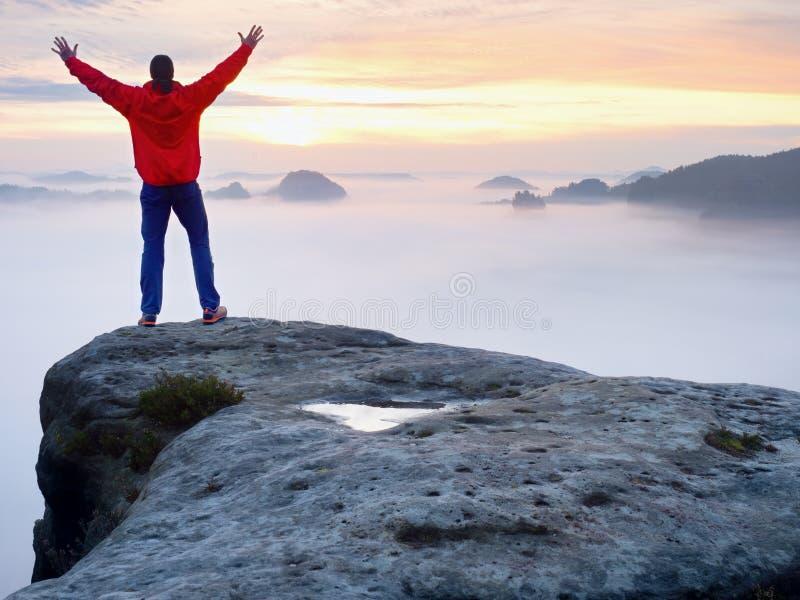 Tylni widok podróżnik samodzielny na falezie z mgły bellow nogami, światło słoneczne w chmurnym niebie obrazy stock