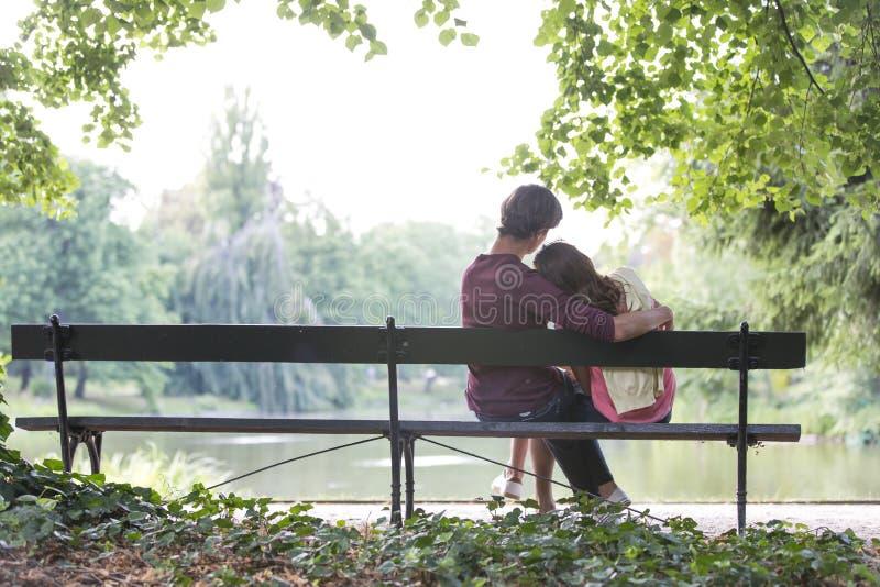 Tylni widok romantyczni potomstwa dobiera się obsiadanie na ławce przy brzeg jeziora obrazy stock