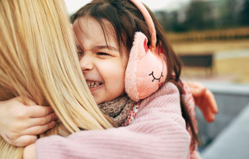 Tylni widok rozochocony szczęśliwy dziewczyna dzieciak obejmuje jej matki outdoors Zamyka w górę portreta kochająca młoda kobieta obrazy royalty free