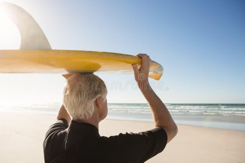 Tylni widok starszego mężczyzna przewożenia surfboard na głowie przy plażą zdjęcia royalty free